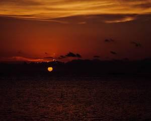 Die Sonne geht hinter den Wolken am Meereshorizont unter und färbt den Himmel rot-orange