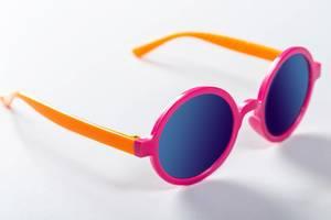 Die Sonnenbrille der Kinder in den hellen Farben auf weißem Hintergrund