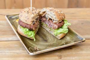 """Die vegan Fleischalternative, Naturbursche-Burger bei """"Hans im Glück"""", durchgeschnitten, mit Blattsalat, Pilzen, Getreide und Erbsenproteinen"""