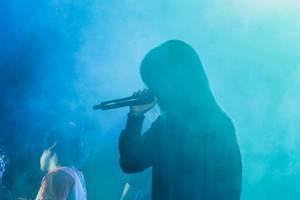 Die von Qualm umhüllte Silhouette einer Sängerin einer Band auf dem Daydream Festival 2018 in Bacolod City