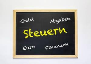 Die Wörter Steuern, Geld, Abgaben, Euro und Finanzen auf einer Tafel