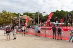 Die Ziellinie eines Triathlons, Menschen warten an Zäunen auf die Ankunft der ersten Läufer