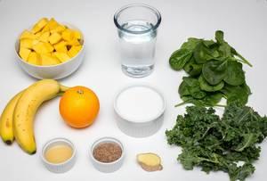 DIe Zutaten für einen gesunden vegan Smoothie - Ananas, Bananen, Orange, Spinat, Grünkohl, Kokosmilch, Leinsamen und Wasser