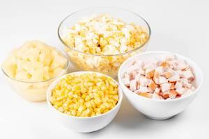 Die Zutaten in Glas- und Keramikschüsseln zur Zubereitung vom Salat mit geräuchertem Hähnchen und Ananas