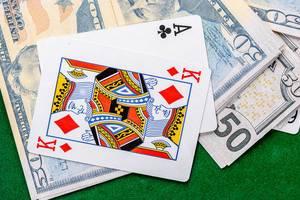 Die zwei Spielkarten Ass und König, liegen auf Dollarscheinen auf einem grünen Pokertisch