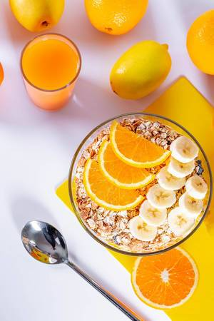 Diet breakfast with porridge and fruit orange, lemon and banana with a glass of fresh juice