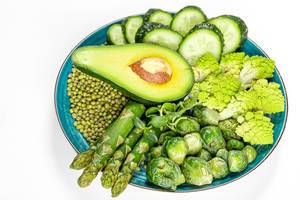 Diet food concept, green fresh vegetables and mung beans in a plate on a white background
