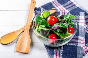 Diet salad with herbs and cherry tomatoes in a glass bowl