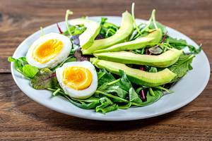 Diet salad with herbs, boiled eggs and avocado