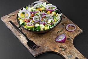 Diet salad with onion, avocado, cucumber and pumpkin seeds on a dark background (Flip 2020)