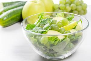 Diet salad with Romaine lettuce, cucumber, grapes and Apple in a glass bowl