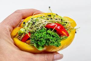Diet vegetarian sandwich with fresh vegetables and micro greens in a woman
