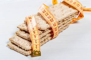 Dietary bread with measuring tape as a symbol of weight loss