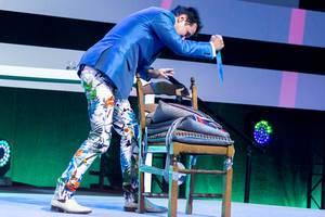Dietmar Dahmen auf der Digital X mit einer Bühnenshow: Sticht mit einem Messer auf ein Stuhl mit Kissen