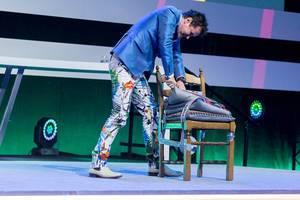 Dietmar Dahmen schneidet in ein Kissen auf der Bühne der Digital X in Köln