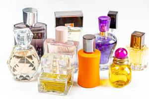 Different perfume bottles on light background