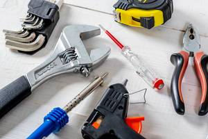 Different Tools such as Hot Glue Gun, Tape Measure, Pliers, Soldering Iron, Hex Keys, Spanner and Screwdriver on a White Wooden Table