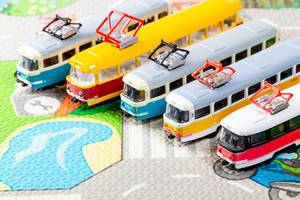 Different toy trams on the carpet to learn the rules of the road