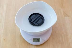 Digitale Küchenwaage und ein Objektivdeckel