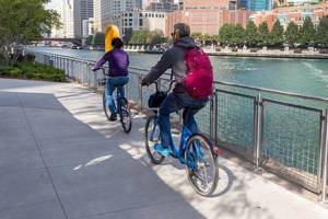 Discovering Chicago by bike: man and woman cycle along the Chicago River on a sunny day using the bike sharing program Divvy