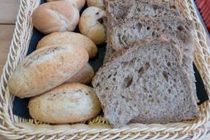Diverse Brötchen und Brotscheiben in einem geflochtenen Brotkorb