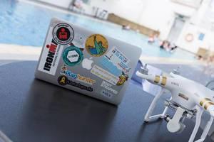 DJI Phantom 3 und MacBook bedeckt mit Reise- und Start-up-Stickern
