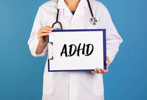 Doctor holding clipboard with ADHD text