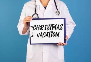 Doctor holding clipboard with Christmas Vacation text
