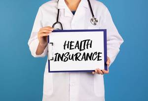 Doctor holding clipboard with Health insurance text