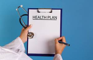 Doctor holding clipboard with Health plan text