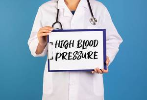 Doctor holding clipboard with High blood pressure text