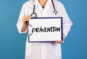 Doctor holding clipboard with Prävention text