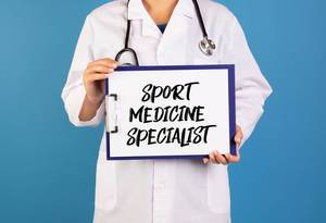 Doctor holding clipboard with Sport medicine specialist text