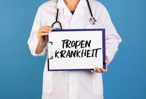 Doctor holding clipboard with Tropen Krankheit text