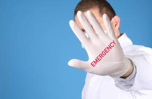 Doctor wearing medical gloves with Emergency text