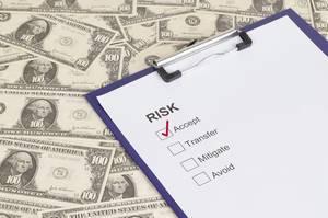 Dokument mit akzeptiertem Risiko angekreuzt auf einem Klemmbrett mit Dollar Geldscheinen als Hintergrund