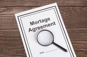 Dokument mit Hypothek Vereinbarung unter einer Lupe und auf einem Holztisch