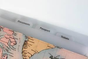 Dokumentenmappe für Reisedokumente wie Tickets und Reisepass mit Weltkarte vor weiß