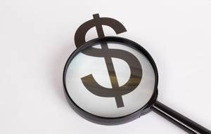 Dollar symbol under magnifying glass