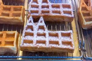 Dom waffles, waffles in the shape of the Cologne Cathedral, some with powdered sugar, on baking grid