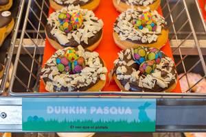 """Donuts mit Schokoglasur und Kokosrasplen """"Dunkin Pasqua"""" verziert mit Osterschmuck in Barcelona, Spanien"""