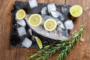Dorado or sea bream fish with lime and lemon slices and sprigs of rosemary. Mediterranean cuisine. Top view (Flip 2019)