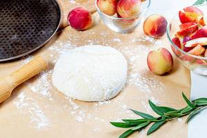 Dough, flour and fresh peaches with rolling pin and baking sheet on the table (Flip 2019)