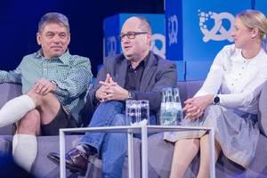 Dr. Lars Krause erzählt während Interview, neben Dr. Carsten Breitfeld und Silja Pieh
