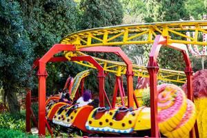 Drachen-Achterbahn für Kinder fährt in Vergnügungspark an Bäumen vorbei