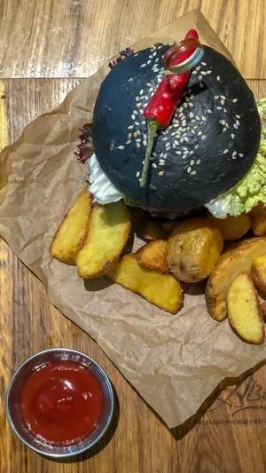 Draufsicht des Veg Kuro Burgers beim Avocado Cafe