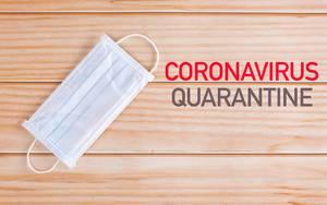 Draufsicht einer Gesichtsmaske neben den Worten Coronavirus Quarantine auf einem Holztisch