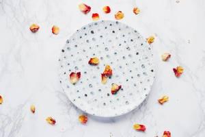 Draufsicht eines bedruckten Tellers mit Blütenblättern auf Marmor