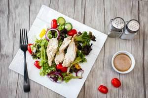 Draufsicht eines Geflügelsalates mit Cherrytomaten, Gurken und Blattsalat