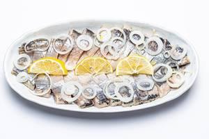Draufsicht eines Tellers mit mariniertem Hering-Filet garniert mit Zitronenscheiben und Zwiebeln auf weißem Hintergrund